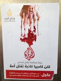 Affiches au Caire montrant le logo de la chaîne qatarie Al-Jazeera avec une main sanglante. « Une balle peut tuer un homme » dit l'affiche « mais une caméra mensongère peut tuer une nation ».  Crédit photo : Kelly McEvers/NPR