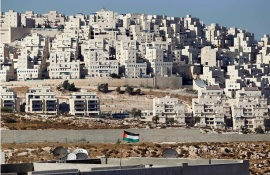 A Palestinian flag flies in front of a settlement known to Israelis as Har Homa and to Palestinians as Jabal Abu Ghneim (Ammar Awad/Reuters)